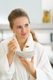 少妇吃muesli画象在厨房里 库存照片