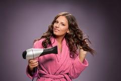 少妇吹干的头发 免版税图库摄影