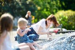 少妇和两个孩子由城市喷泉 免版税库存照片