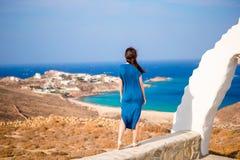 少妇和传统白色教会有海视图在米科诺斯岛海岛,希腊 库存图片