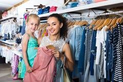 少妇和女孩在衣裳商店 免版税库存图片