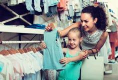 少妇和女孩在衣裳商店 库存照片