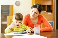 少妇和她的儿童绘画与水彩 库存图片