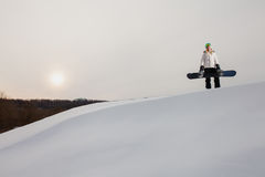 少妇和她的雪板在积雪的山腰 免版税库存图片