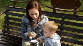 少妇和孩子在长凳的一个公园吃着冰淇凌 年轻母亲哺养她儿子与匙子的冰淇凌 影视素材