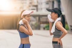少妇和毛巾呆在一起在锻炼以后 健身和健康生活方式概念 库存照片