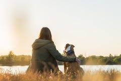 少妇和狗享受自然视域在黎明靠近湖 图库摄影