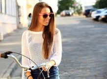 少妇和自行车在城市 免版税库存图片