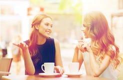 少妇喝咖啡和谈话在咖啡馆 库存图片