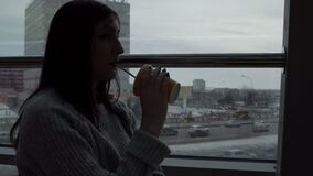 少妇喝在咖啡馆的新近地被紧压的汁液,看在特大的城市背景的窗口 影视素材
