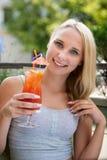 少妇喝鸡尾酒室外在一个热的夏天下午  图库摄影