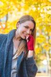 少妇在一个五颜六色的秋天庭院里 免版税库存照片