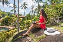 少妇在一个热带庭院里读一本书 库存图片