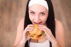 少妇在一家美好的用餐的餐馆吃一个汉堡包,她不适当地表现 免版税库存图片