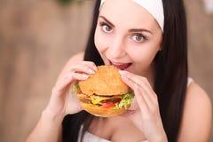 少妇在一家美好的用餐的餐馆吃一个汉堡包,她不适当地表现 免版税图库摄影