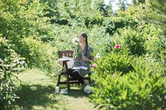 少妇在一把椅子的庭院里休息与一个杯子te 库存图片