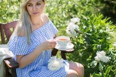 少妇在一把椅子的庭院里休息与一个杯子te 免版税库存照片