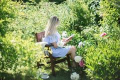 少妇在一把椅子的庭院里休息与一个杯子te 免版税图库摄影