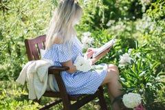 少妇在一把椅子的庭院里休息与一个杯子te 库存照片