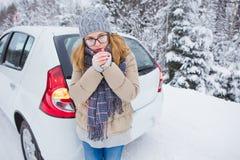 少妇在一条积雪的冬天路停留在汽车旁边并且温暖她的手 免版税图库摄影