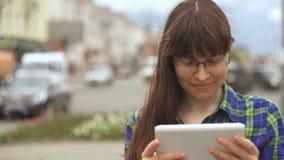 少妇在一条繁忙的路旁边享用一种数字式片剂 股票录像