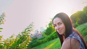 少妇在一棵绿色树附近嬉戏地跑在庭院里 一个微笑的浅黑肤色的男人的画象有起波纹的面颊的反对 影视素材