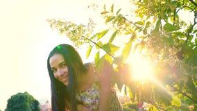 少妇在一棵绿色树附近嬉戏地跑在庭院里 一个微笑的浅黑肤色的男人的画象有起波纹的面颊的反对 股票视频