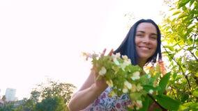 少妇在一棵绿色树附近嬉戏地跑在庭院里 一个微笑的浅黑肤色的男人的画象有起波纹的面颊的反对 股票录像