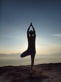 少妇在上午执行在峭壁的瑜伽 免版税图库摄影