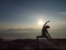 少妇在上午执行在峭壁的瑜伽 图库摄影