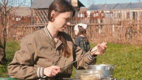 少妇在串上把肉放 烹调猪肉kebabs  走动她的女儿 影视素材