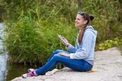 少妇在优秀精神上使用一个电话并且听到音乐 免版税库存图片