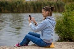 少妇在优秀精神上使用一个电话并且听到音乐 免版税库存照片