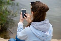 少妇在优秀精神上使用一个电话并且听到音乐 库存照片