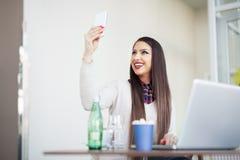少妇在使用手机的办公室 图库摄影