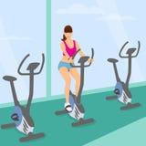 少妇在健身房使用一辆自行车为好m 库存图片
