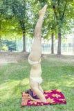 少妇在公园做手倒立 免版税库存图片