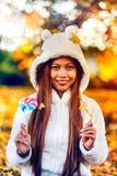 少妇在公园在晴朗的秋天天,微笑,拿着叶子和糖果 白色毛线衣的快乐的美丽的女孩在pa 免版税库存图片
