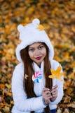 少妇在公园在晴朗的秋天天,微笑,拿着叶子和糖果 白色毛线衣的快乐的美丽的女孩在pa 库存图片