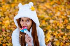 少妇在公园在晴朗的秋天天,微笑,拿着叶子和糖果 白色毛线衣的快乐的美丽的女孩在pa 图库摄影
