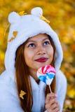 少妇在公园在晴朗的秋天天,微笑,拿着叶子和糖果 白色毛线衣的快乐的美丽的女孩在pa 库存照片