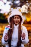 少妇在公园在晴朗的秋天天,微笑,拿着叶子和糖果 白色毛线衣的快乐的美丽的女孩在pa 免版税图库摄影