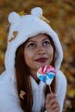 少妇在公园在晴朗的秋天天,微笑,拿着叶子和糖果 白色毛线衣的快乐的美丽的女孩 免版税图库摄影