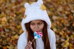 少妇在公园在晴朗的秋天天,微笑,拿着叶子和糖果 白色毛线衣的快乐的美丽的女孩 免版税库存图片