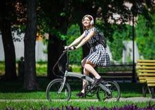 少妇在公园骑自行车 免版税图库摄影