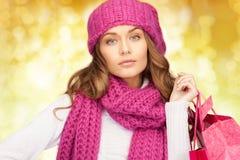 少妇在冬天穿衣与购物袋 免版税库存图片