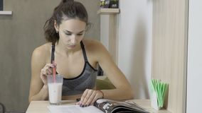 少妇在厨房里读坐在桌上的杂志 影视素材