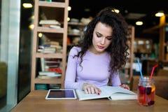 少妇在咖啡店的阅读书 免版税库存图片