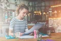 少妇在咖啡馆坐在木桌和读上 女孩在餐馆等待朋友,同事 免版税库存图片