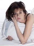 少妇在唤醒疲乏的失眠宿酒的床上 免版税库存照片